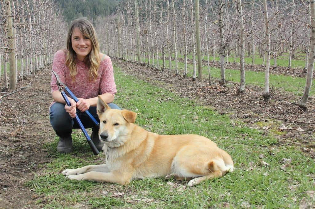 Melissa and pup in their orchard